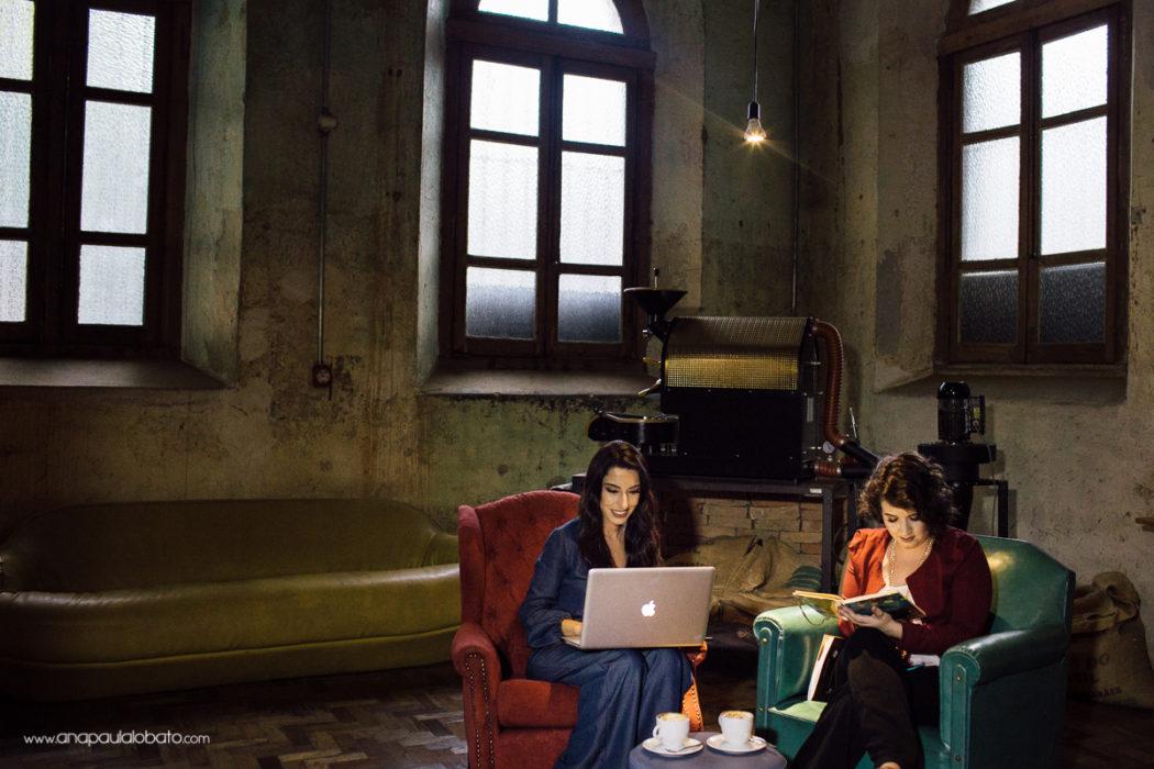 Amigas trabalhando com macbook e lendo livro