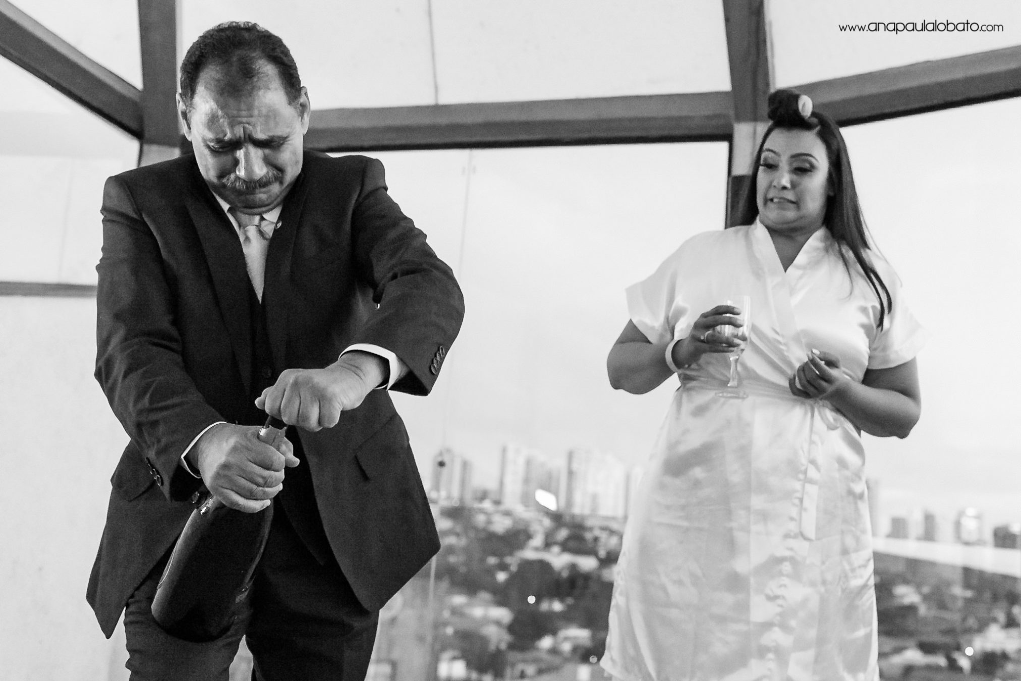 Father of the bride trying to open a bottle of champagne