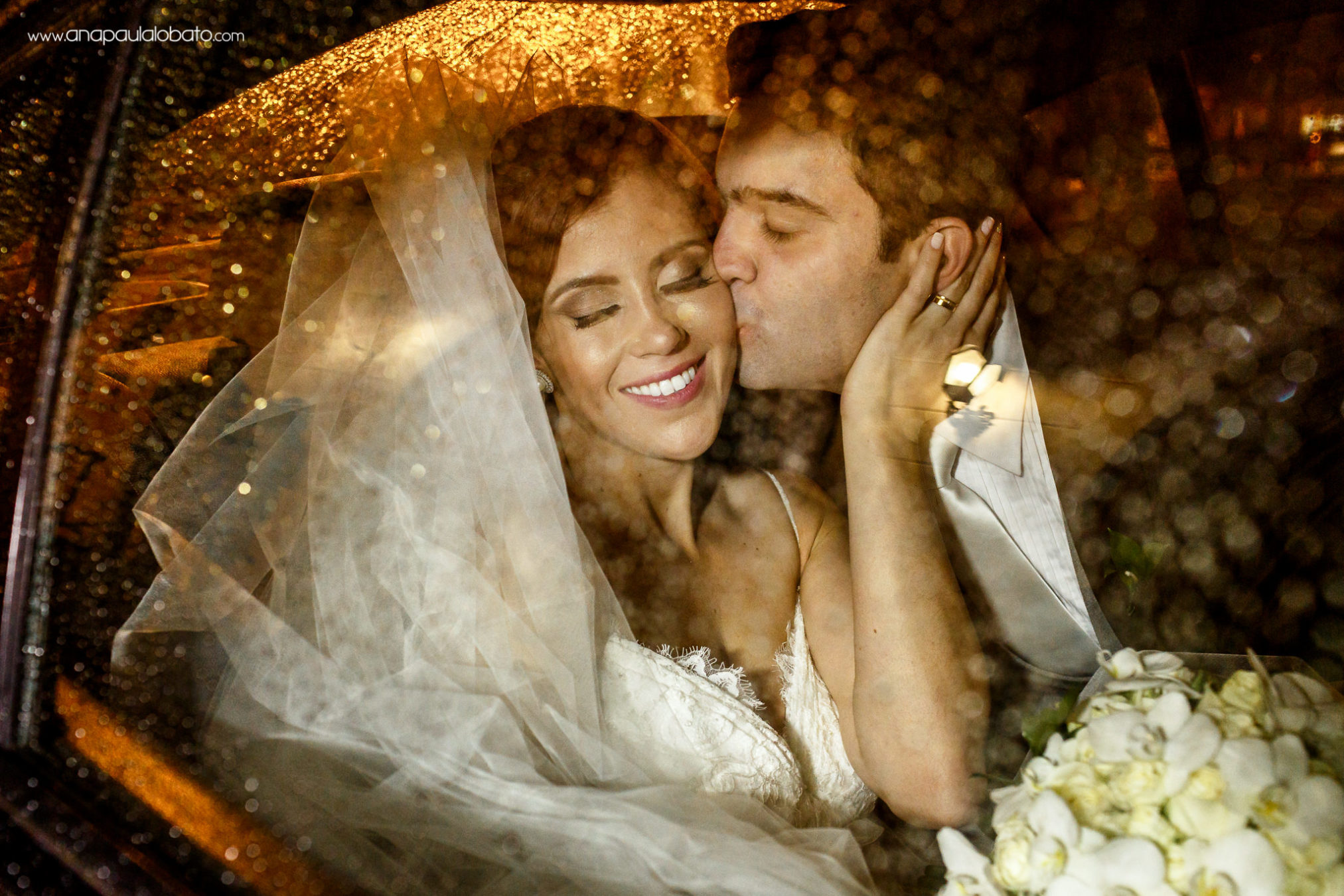 Just married couple kisses inside the car with water drops