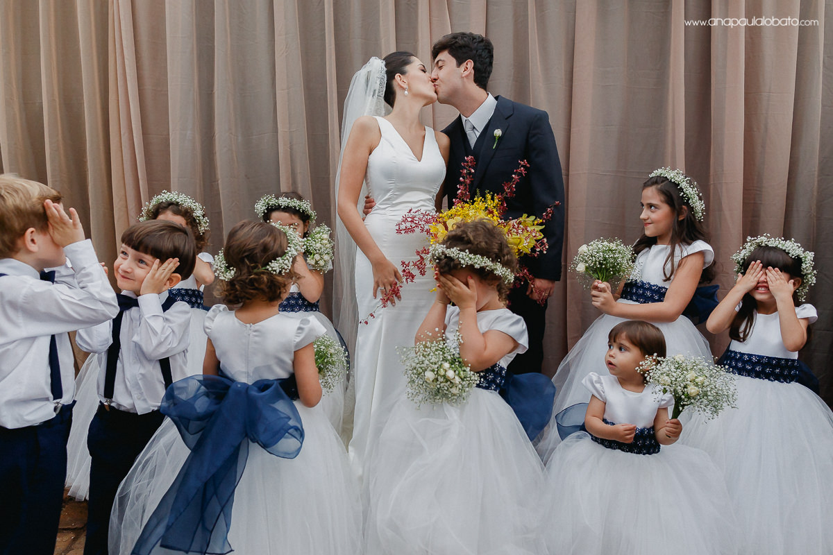 Kids being funny while married couple kisses