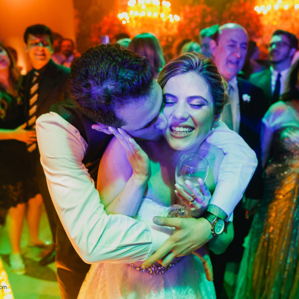 Groom hugs and kisses the bride in a colorful moment