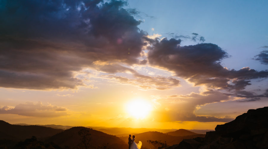 Couple looking at each other in a perfect moment being lit by incredible colors of the sunset